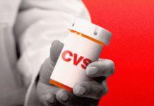 Un medecin présentant une boîte à comprimés CVS.